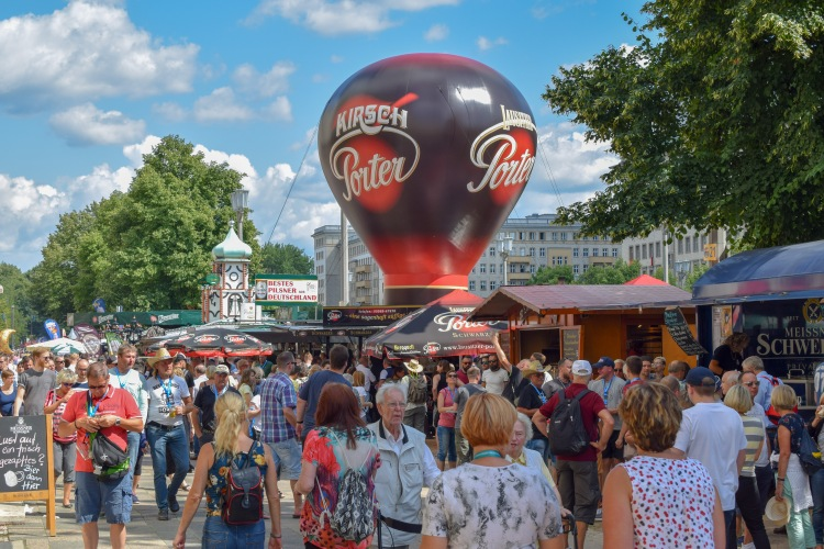 Crowds at the Berlin Beer Festival walking down the Beer Mile with a large promotional balloon in the background on a sunny day