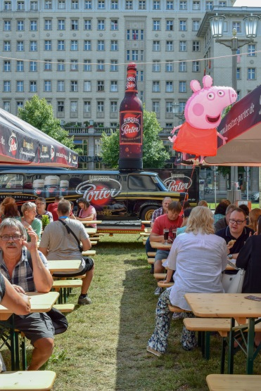 Crowds drinking beer at Berlin Beer Festival with a Peppa Pig balloon