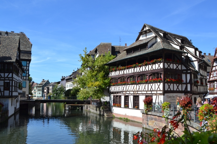 Strasbourg view of a historical house with flowers at the windows in front of a river