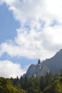 Castle on top of a hill near Munich with green forest trees below and cloudy skies