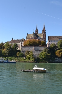A view of Switzerland on the river with a boat and a church with spires on the background