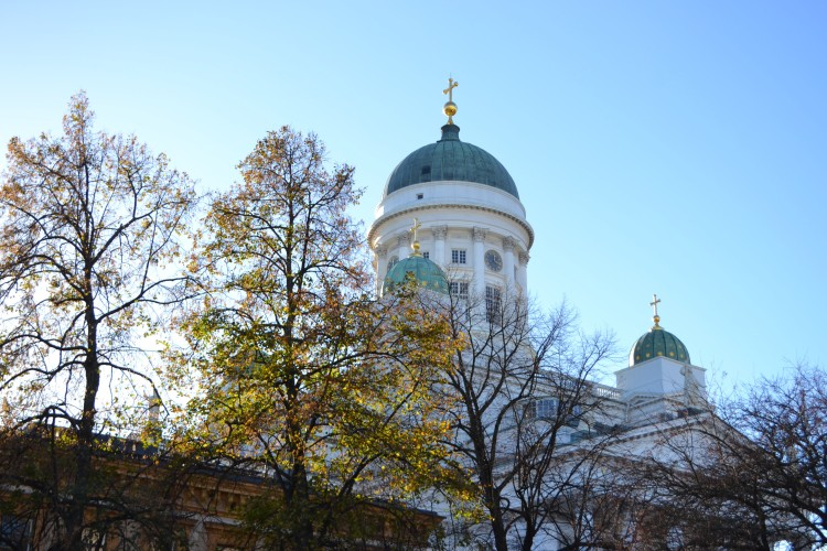 Helsinki Cathedral in the Sun white with a domed roof with trees obscuring the view in Finland