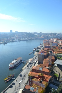 View from the bridge in Porto with the boats below on the river and the Port cellars over the other side