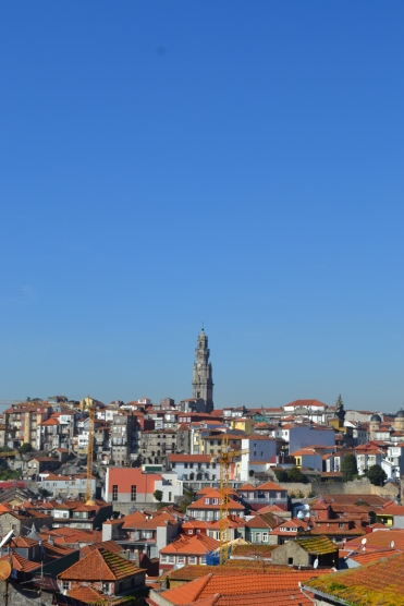Panorama of the view from the hill in Porto Portugal with the orange terracotta roof tiles and the spire in the distance on the horizon