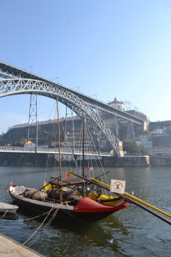 Hazy view of the river in Porto with a view of the bridge in the distance and a boat on the river water