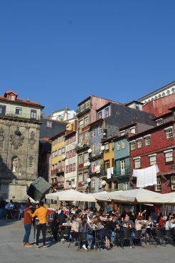 Colourful buildings in Porto by the river side with outside dining where the tourists eat their dinner in the sunshine in Portugal