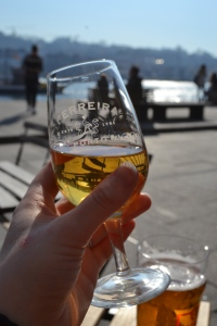 Cheers in Porto a small port glass by the river side in the sun