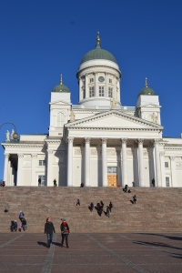 Steps up to Helsinki Cathedral white building very grand with lots of steps leading to it with lots of tourists in the winter walking up to the church Finland