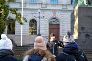 Free Walking Tour in Helsinki Finland man talking about the history of the city in front of a crowd of people wearing bobble hats in winter