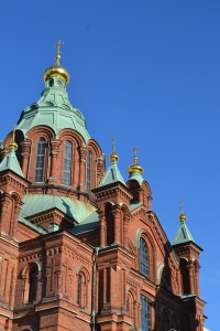 Church in Helsinki red brick with green copper roof in the sun in winter with blue sky