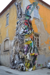 Creative Street Art in Porto Portugal of a rabbit made out of rubbish and objects on a wall huge street art