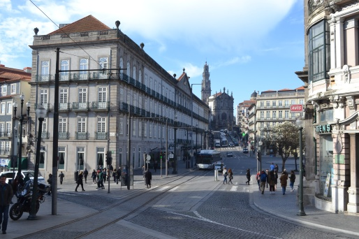 Street view in Porto Portugal in the morning with people walking through the street and a view up to the church in the distance