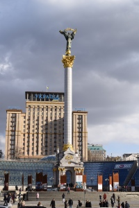 Independence Square in Kyiv in Ukraine with black clouds in the sky and tourists walking around