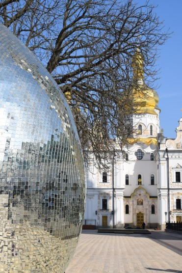 A church and a shiny mosaic egg sculpture art at the Lavra Complex in Kyiv Ukraine