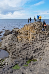 group of tourists climibing over the balsalt colomns at the giants causeway northern ireland