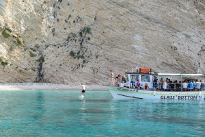 Clear water with a boat against some white cliffs man jumping in the water from the edge of the boat