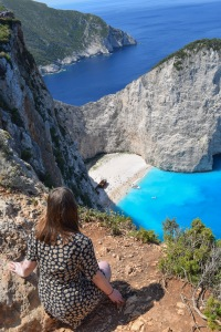 Girl looking over the top of a cliff down to Navagio Beach Shipwreck Beach with blue sea and white sand