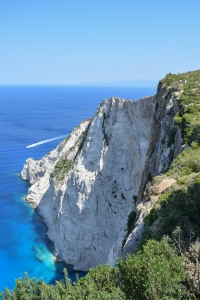 Viewpoint high up on the cliff overlooking the blue sea and steep white cliffs with a boat in the distance