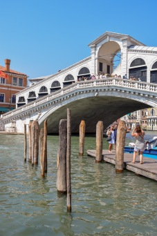 A view of Rialto Bridge the white arched bridge in venice that goes over the grand canal with tourists taking a photograph in front