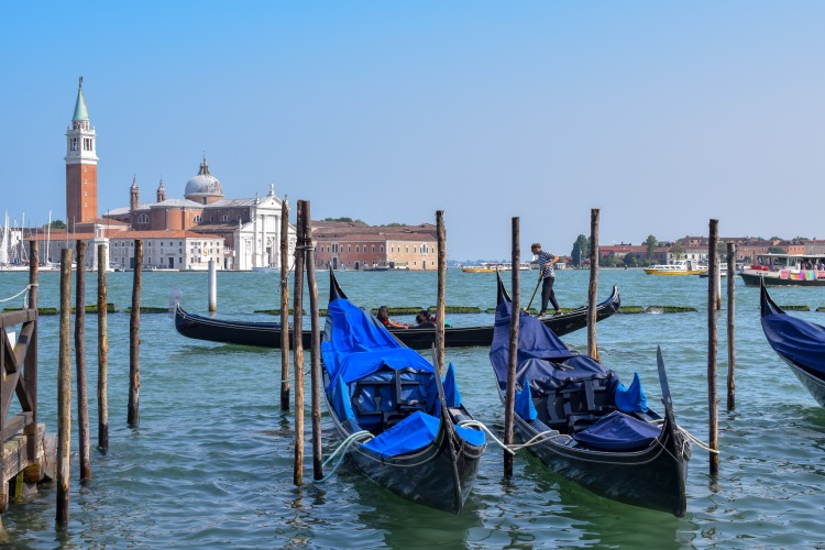 A view of the Gondolas in Venice on the blue water on a summers day in the sunshine