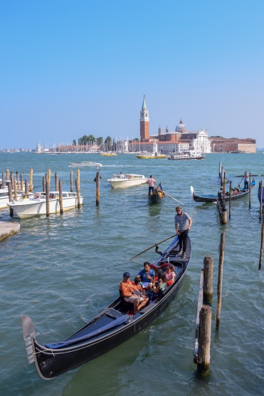 A classic view of Venice with three Gondolas in the canal in the water on a sunny day in the summer