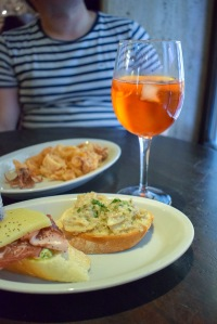 A close up of some tasty small plates of tapas Cicchetti in Venice with an orange drink on the table