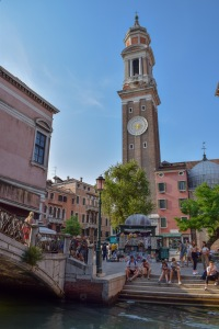 A sunny evening in Venice in Italy next to the canal with people sat on the floor on some steps, with a clock tower in the background