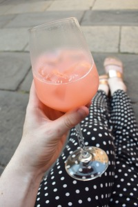 Girl in Spotty trousers drinking a Bellini in Venice whilst sat on the pavement outside at bar in Italy